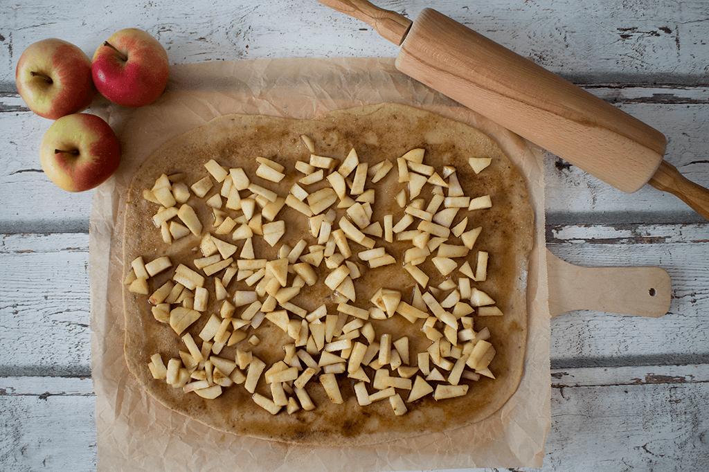 Den Teig ausrollen und mit Äpfeln und Zimtmischung bestreichen