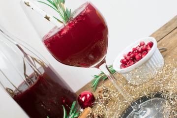 Champagnercocktail mit Zimt, Sternanis, Cranberries und Rosmarin